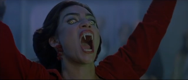 Beutiful dark haired woman with yellow eyes and long vampire fangs, in a red dress, opening her mouth wide and looking at the camera.